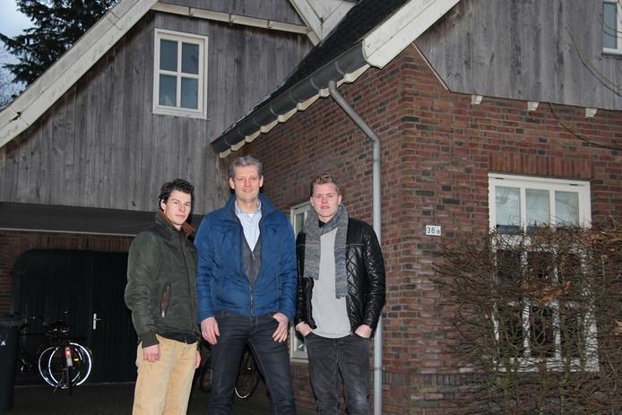 Wethouder Volmerink (midden) poseert voor de voormalige dienstwoning van het hotel met de beide broers.