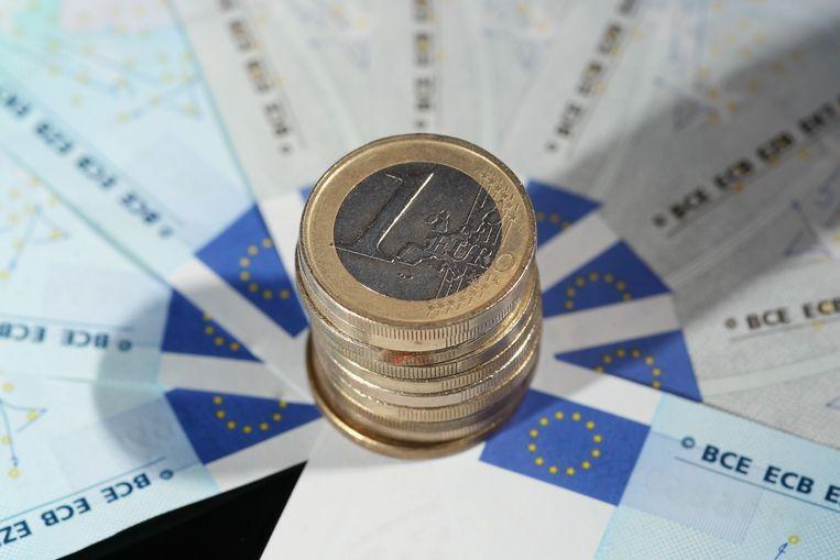 Een stapeltjes euro's met daaronder briefjes van 5 euro. Beeld Getty Images