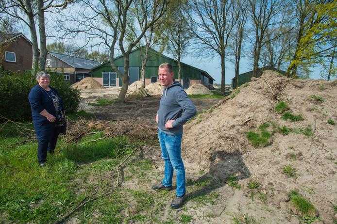 Karen van Bokhoven en zoon Dirk op de plek waar parkeerplaats en terras komen, op de achtergrond de stallen.