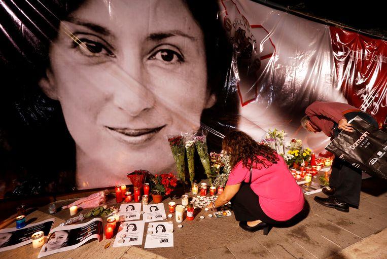 Mensen leggen bloemen en branden kaarsen bij een geïmproviseerde herdenkingsplek voor de onderzoeksjournaliste Daphne Caruana Galizia, die in 2017 op Malta werd vermoord.  Beeld REUTERS