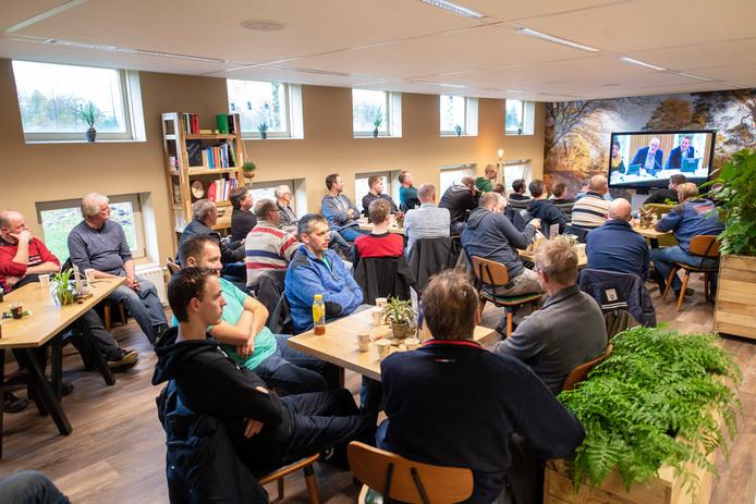Protesterende boeren volgen de vergadering van Waterschap Vallei en Veluwe op een scherm in de kantine.