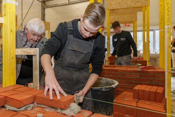 Klaas Heutink (81) kijkt over de schouder van Dylan Sempel (16) mee of het metselen goed gaat.