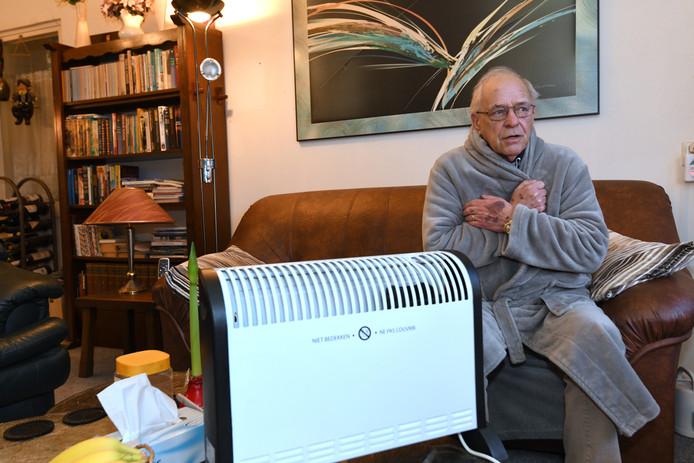 Een kamerjas en elektrische kachel houden Henk Leenders nog enigszins warm.