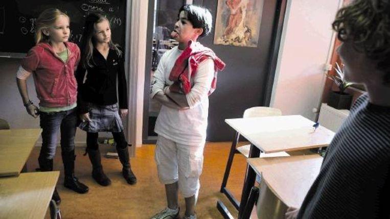 Laurens de Koste van de Paschalisschool in Den Haag laat zien hoe, volgens hem, sommige inheemse volken elkaar groeten. Linde Tangelder, met rechts naast haar Victorina Dumoulin, en Just Hopmans kijken toe. (FOTO'S JOÃ¿L VAN HOUDT) Beeld