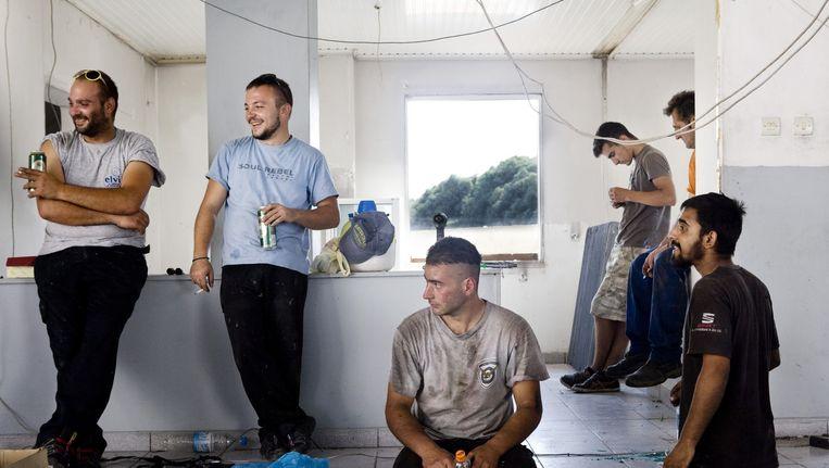 Iannis Pourouris (uiterst links) in de garage. Beeld Io Cooman
