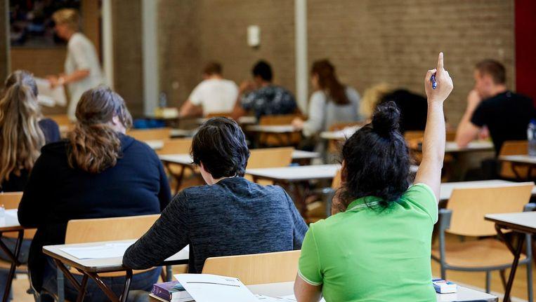 Leerlingen van Havo 5 doen in de gymzaal van hun school eindexamen in het vak Maatschappijwetenschappen. Beeld anp