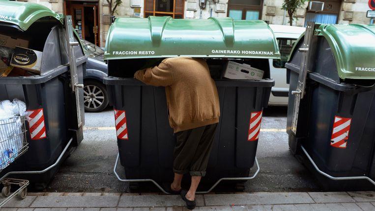 Een man zoekt naar eten in een afvalbak in Bilbao, Spanje. Beeld Reuters