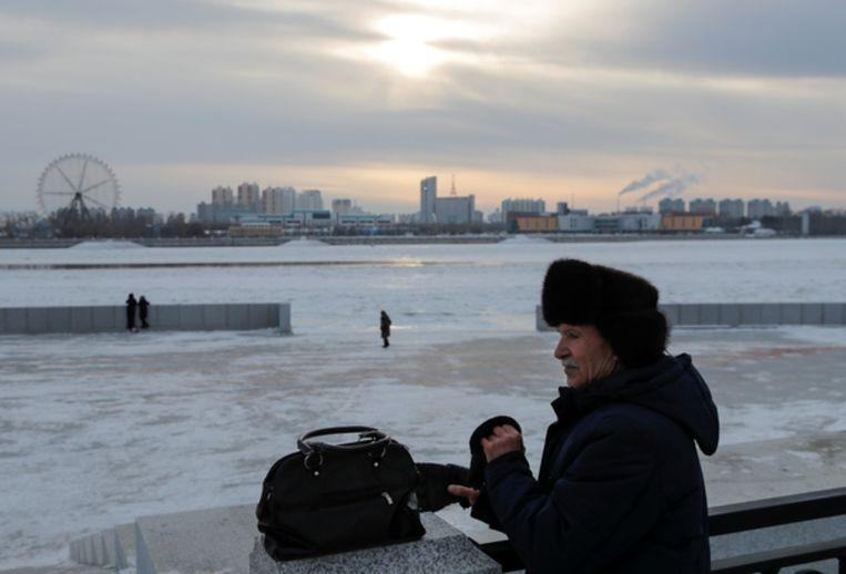 Een man staat aan de oever van de bevroren Amur rivier in Blagoveshchensk. Op de achtergrond is de Chinese grensstad Heihe te zien.  Beeld REUTERS