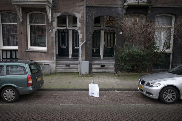 Een bewoner houdt in Amsterdam een parkeerplek vrij door middel van een tas. Beeld Joost van den Broek