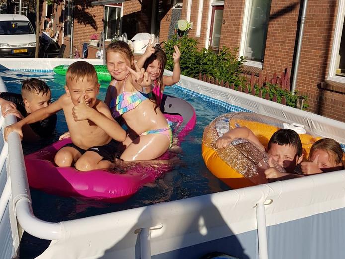 Kinderen uit de wijk het Rode Dorp vermaken zich in het door de buurt neergezette zwembad aan de Landstraat in Deventer.