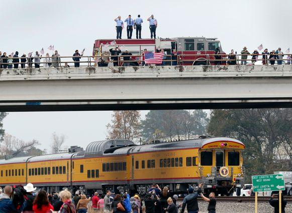 Brandweermannen staan op hun truck en salueren Bush, die ligt opgebaard in de trein die onder het viaduct doorrijdt.