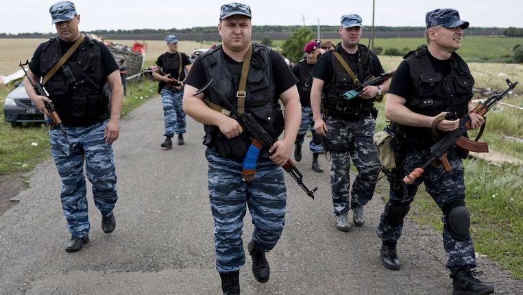 Gewapende mannen, voormalige leden van het opgeheven Oekraïense elite-politiekorps Berkut, begeleiden een uitgebreide OVSE-missie Beeld ANP