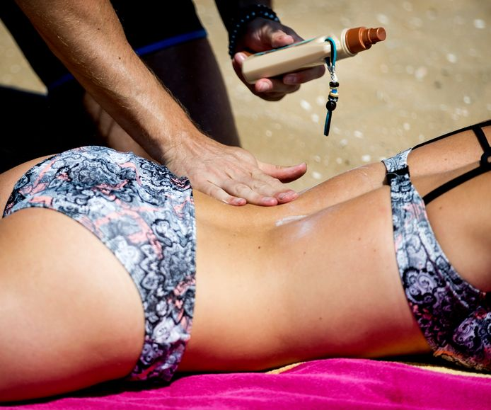 Een badgast wordt op het strand ingesmeerd met zonnebrandcrème.