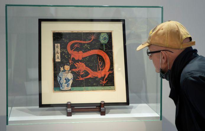 Een bezoeker bekijkt de cover van 'De Blauwe Lotus' in het veilinghuis Artcurial in Parijs, waar de cover geveild werd.