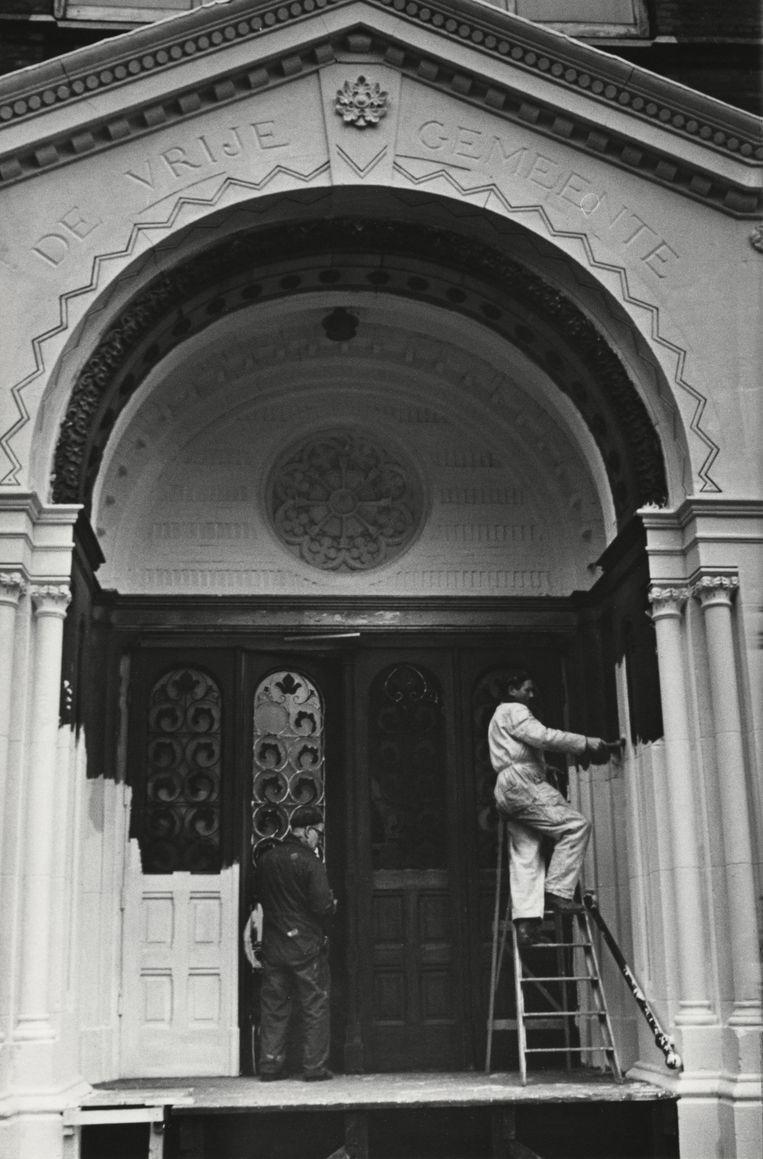 Fred Wessels, hoogstwaarschijnlijk in witte overall, schildert de ingang feloranje, 1968.  Beeld Nationaal Archief/Collectie Spaarnestad/Anefo/Fotograaf onbekend
