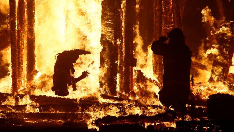 De brandweerman rechts kon niet voorkomen dat de man (links) de vlammen insprong.