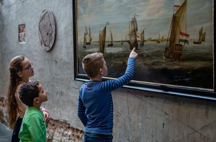 Kinderen bekijken een oude meester met schepen op de rede van Vlissingen in het Atrium van het MuZEEum.