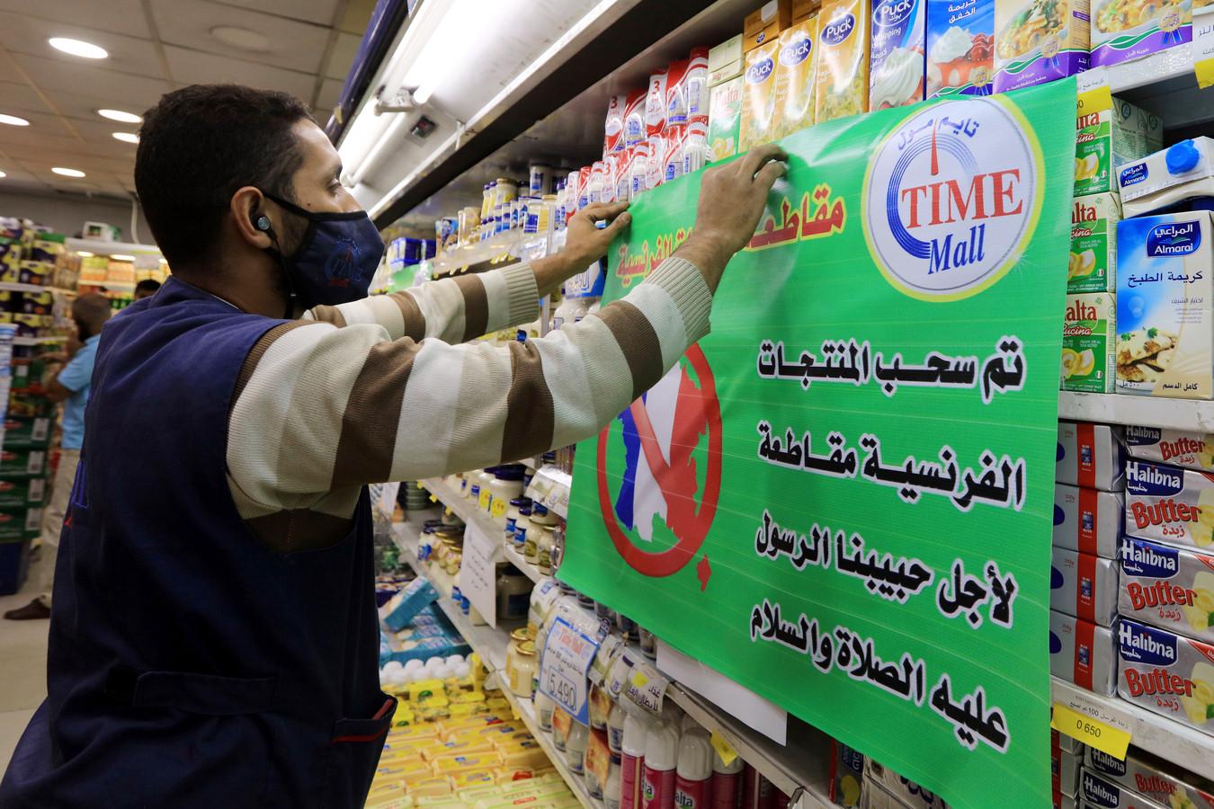 Een supermarktmedewerker in Amman, Jordanië, hangt een papier op dat meldt dat Franse producten worden geboycot.