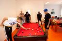 Bayamin, Zain en Quiermo (vlnr) spelen voor de foto een potje biljart in het jeugdcentrum in Zevenhuizen. Normaal kan dat niet, omdat het centrum vanwege corona al weken op slot zit. Op de achtergrond jongerenwerkers Wilco Boers (links) en Joselito Hasselnook.