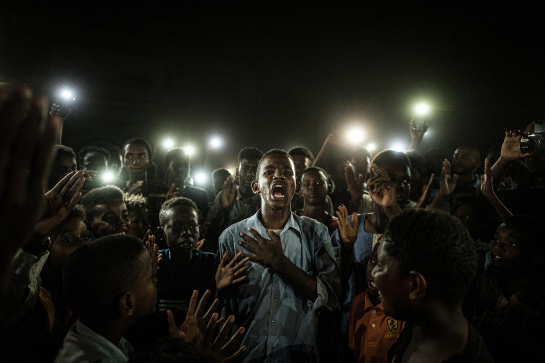 De winnende foto: een demonstrant leest een protestgedicht voor in de Soedanese hoofdstad Khartoem. Beeld Yasuyoshi Chiba / AFP