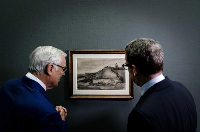 John Fentener van Vlissingen (links) en Axel Rüger van het Van Gogh Museum in januari dit jaar in Laren bij de onthulde tekening van Vincent van Gogh: 'De heuvel van Montmartre met steengroeve'.