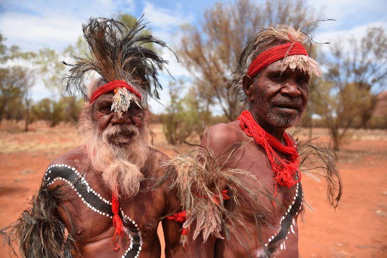 Aboriginals poseren voorafgaand aan een dans bij Uluṟu, een bekende grote rotsformatie in het midden  van Australië. Voor de lokale Aboriginals is Uluru een belangrijke religieuze plaats. Beeld EPA