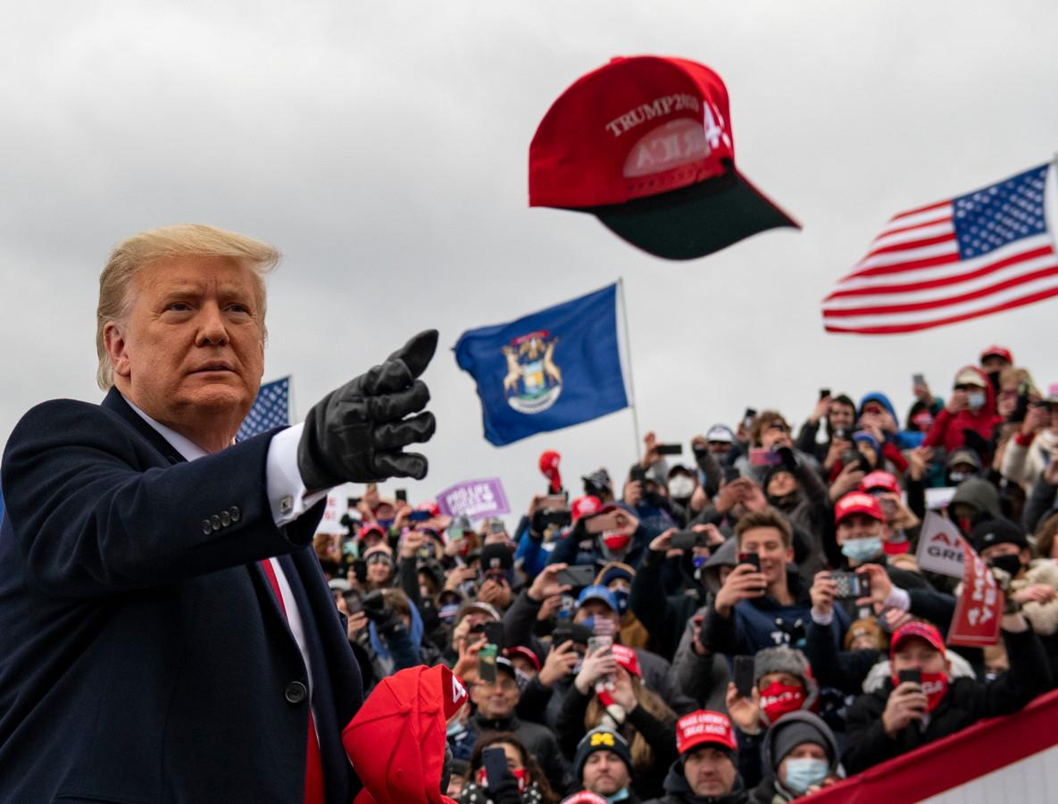 President Donald Trump gooit een van zijn befaamde caps richting zijn aanhang tijdens de campagnebijeenkomst in Waterford Township, in de Amerikaanse staat Michigan.