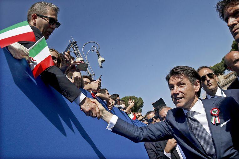 De nieuwe premier Giuseppe Conte groet het publiek tijdens de viering van de Dag van de Republiek. Beeld null