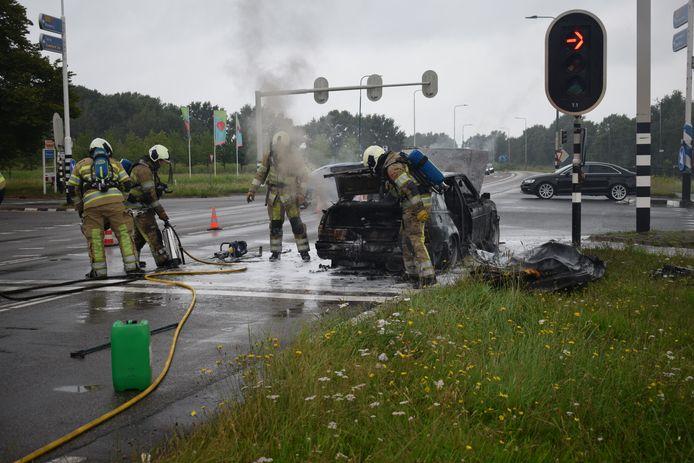Brandweerlieden bij de uitgebrande auto in Rhenen.