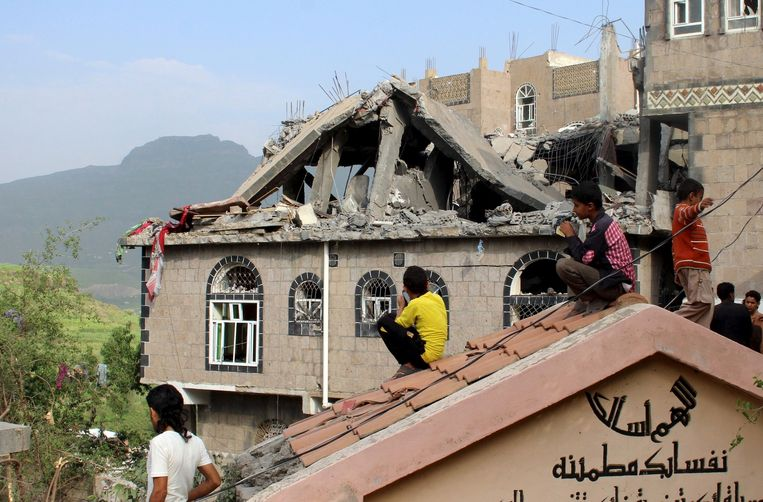 Burgers in Jibla naast een beschadigd huis door luchtaanvallen.