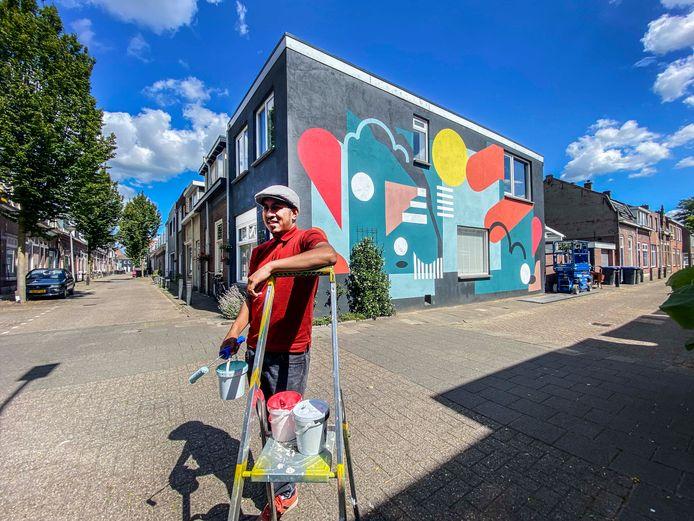 """Eerst grijs en grauw, nu kleur: Aziz Lessy nam een muur aan de Klaverstraat onder handen. De bewoners stelden de muur ter beschikking. ,,Je merkt het al als je aan het werk bent: alleen maar complimenten van voorbijgangers, vrolijke gezichten."""""""