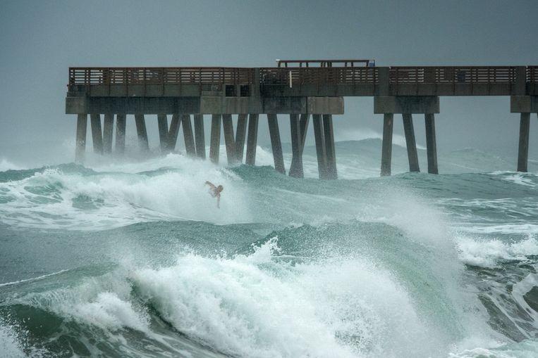Een surfer langs de kust van Florida tijdens Isaias. Beeld EPA