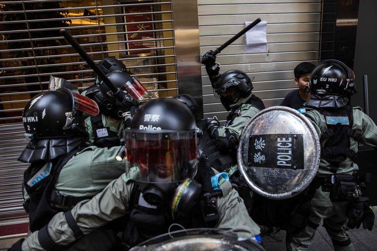De Hongkongse oproerpolitie zet met geweld twee betogers klem. Beeld AFP
