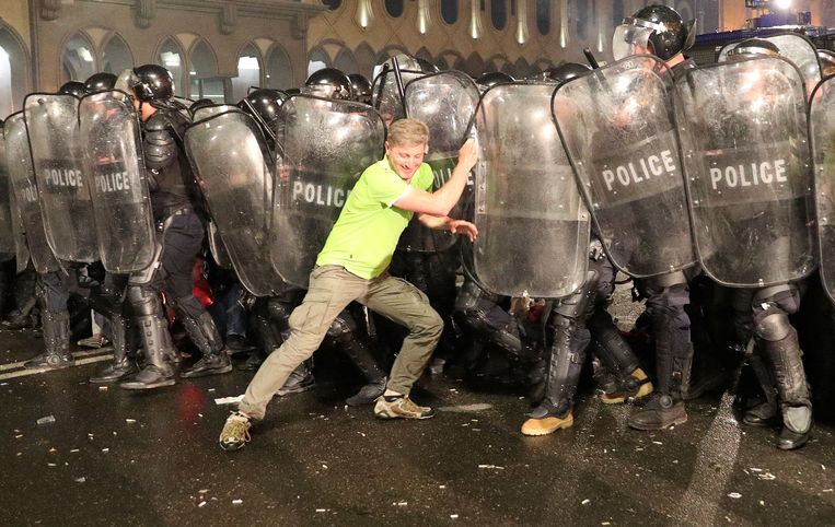 Een demonstrant in Tblisi neemt het in zijn eentje op tegen een politiecordon. Beeld REUTERS