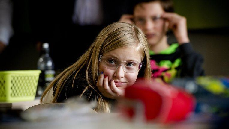 en leerlinge van basisschool De Plevier luistert met een vuurwerkbril op naar het verhaal van een oogarts van Het Oogziekenhuis Rotterdam Beeld ANP