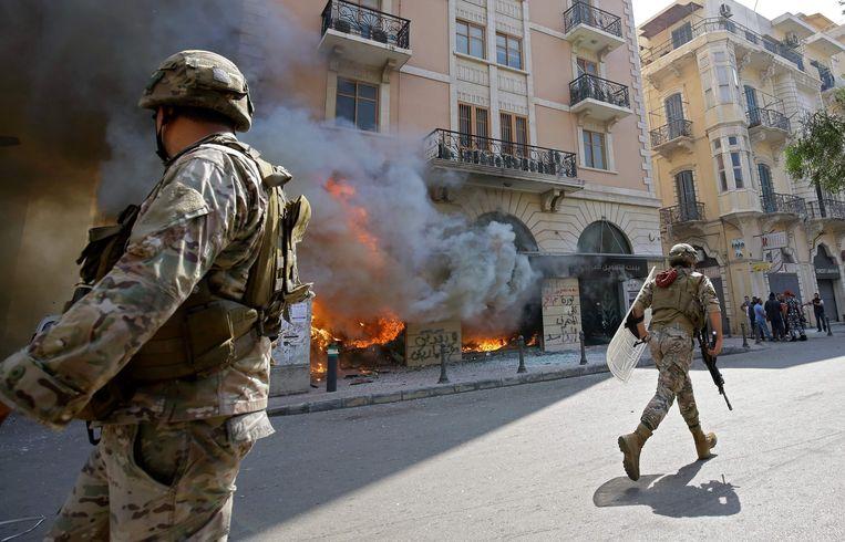 Libanese soldaten bij een door demonstranten in brand gestoken bankgebouw in Tripoli, afgelopen week. Beeld AFP