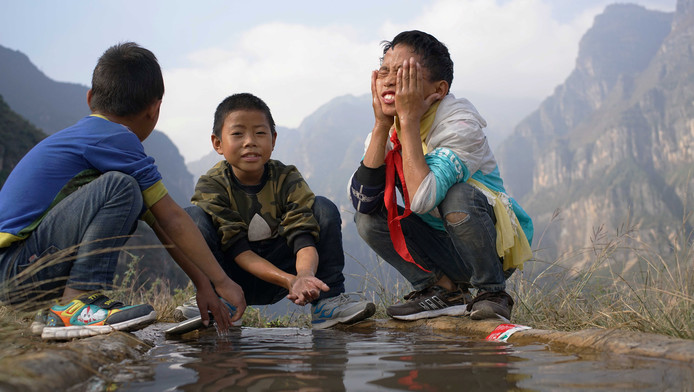 Kinderen van het dorpje rusten uit na de flinke beklimming