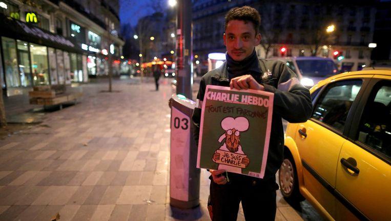 De verkoop vanochtend in Parijs van de eerste exemplaren van Charlie Hebdo. Beeld getty