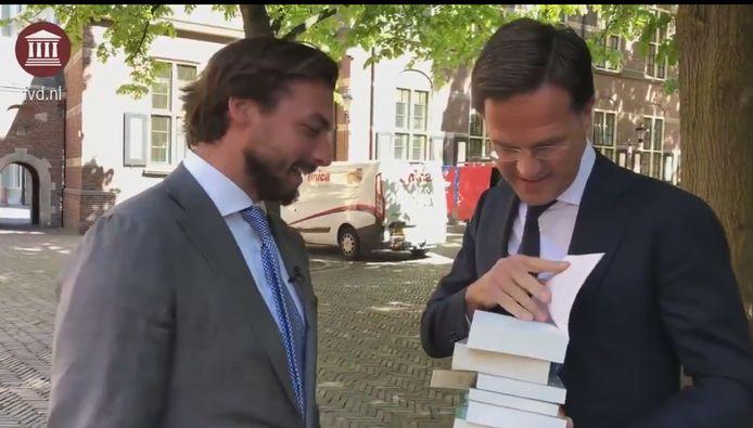 Thierry Baudet geeft zijn boeken aan premier Mark Rutte. ,,Huiswerk voor het debat,'' aldus de FvD-leider.