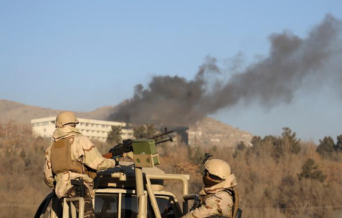 Afghaanse commando's bewaken de toegangsweg naar het hotel, waaruit dikke zwarte rookwolken opstijgen
