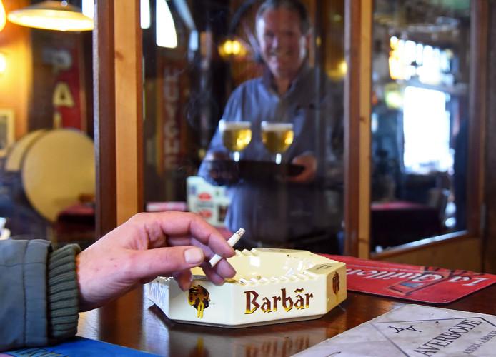 Ronnie Verberkmoes, op de achtergrond, heeft in café De Vriendschap een rookruimte gebouwd.