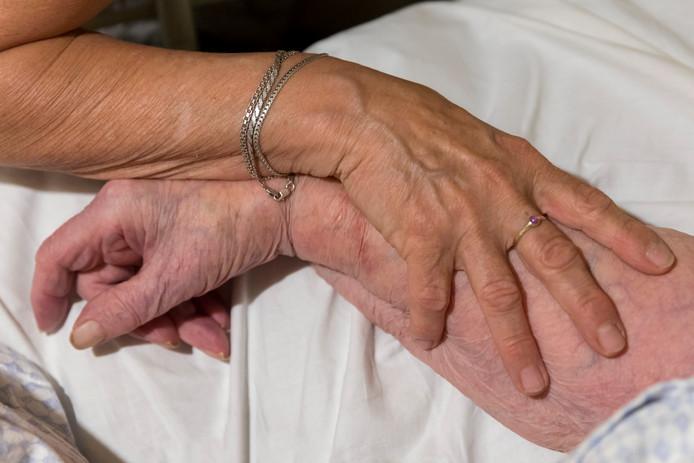Sjan van Bergen, vrijwilligsters bij VPTZ, ondersteunt stervende mevrouw. Foto Marc Bolsius