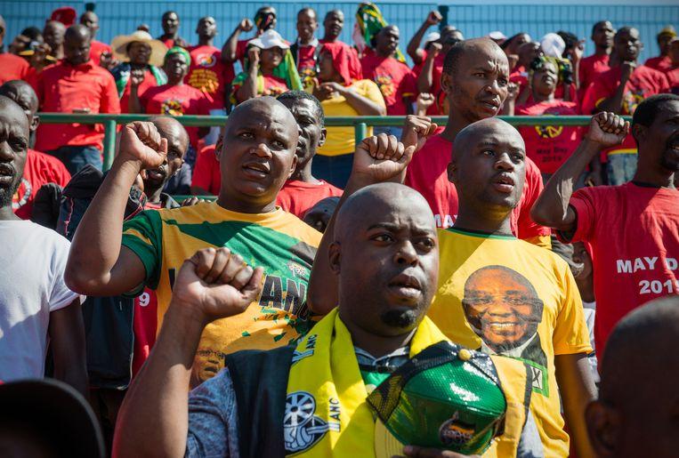 ANC-leden Vuyani Ngwenya (linksmidden) en Nkosinathi Madonsela (rechtsmidden) bij een partijbijeenkomst in Katlehong. De vrienden steunen ieder een andere partijprominent. Beeld Bram Lammers