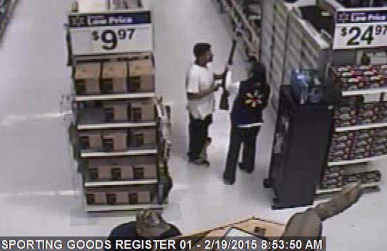 Een verkoper in een Wal-mart wil een geweer afpakken van Mario Valencia, een man uit Arizona die in april door de politie werd klemgereden. Beeld epa