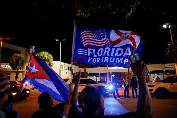 Een Trumpsupporter houdt een Cubaanse vlag en een Trumpvlag vast.