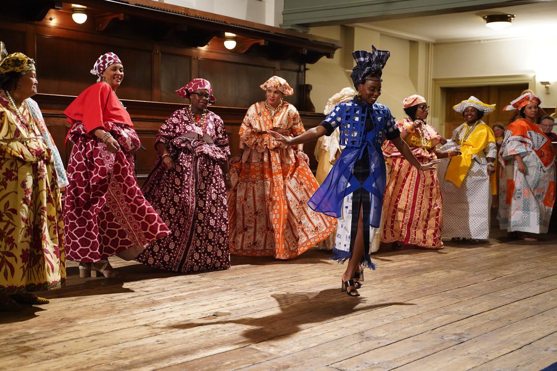 Vrouwen voeren een dans uit bij de opening van de tentoonstelling. De vrouw vooraan danst in een kledingstuk dat de aan de tentoonstelling gekoppelde ontwerpwedstrijd heeft gewonnen. Beeld Het Klederdrachtmuseum / Paul Enkelaar