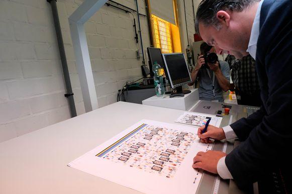 Philippe Debacker signeert een  vel met nieuwe zegels.