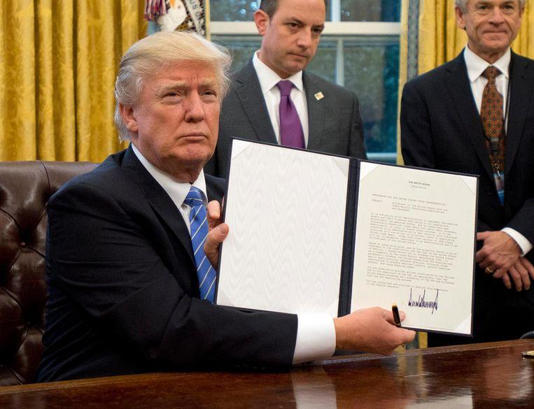 Trump poseert met decreet waarmee de VS zich terugtrekken uit TPP. Beeld getty