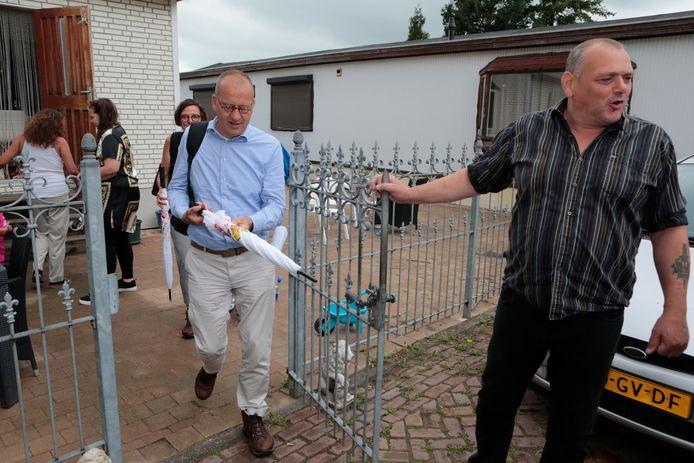 Piet van Assendorp leidt burgemeester Segers van Molenlanden rond op het woonwagenkamp in Arkel.