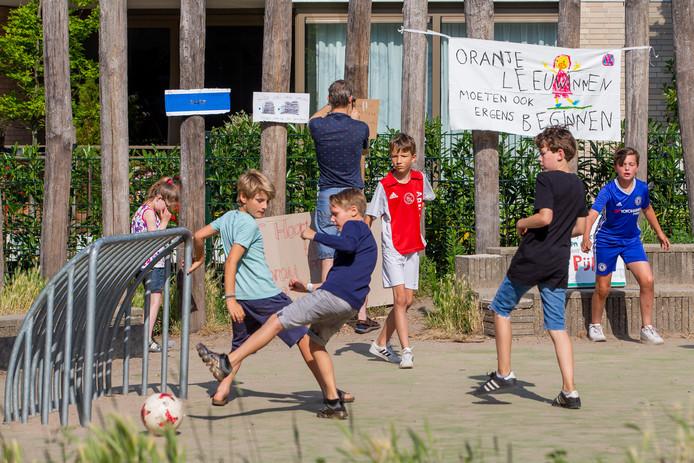 Leerlingen van De Buut spelen op het trapveldje van de basisschool naast het appartementencomplex.
